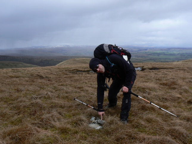 My friend Matt pointing to the small pile of stones on the summit of West Fell