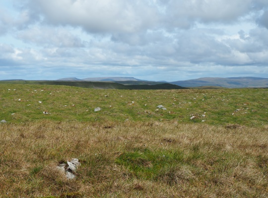 The small pile of stones on the 596m spot height with slightly higher ground to the left