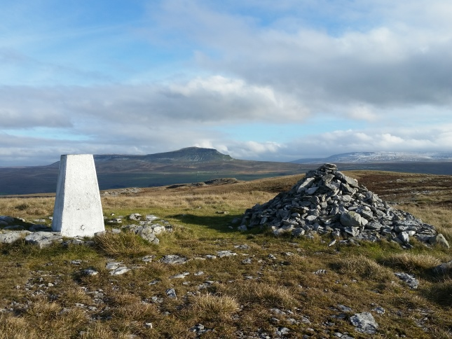 The trig point and summit cairn on Moughton looking towards Pen-y-ghent