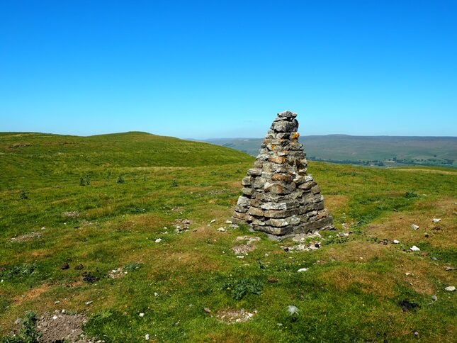 A cairn, possibly made from the old trig point, with the summit in the background