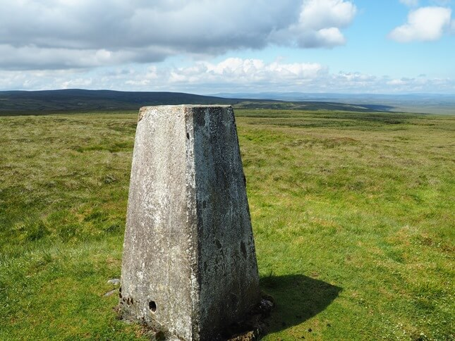 Looking over the wall at the trig point with Water Crag in the distance