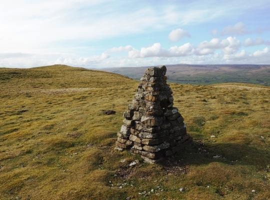 The cairn built from the former trig point with the summit of Addlebrough beyond