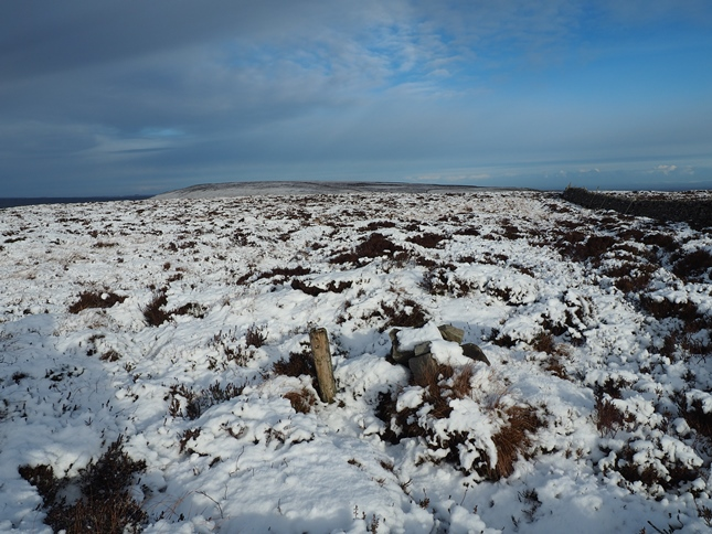 The top of Harland Hill with the small pile of stones buried in the snow