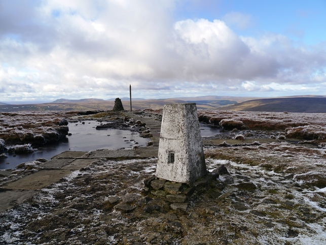 The trig point, cairn and wooden stake on the summit