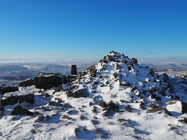 The trig point is dominated by the neighbouring summit cairn