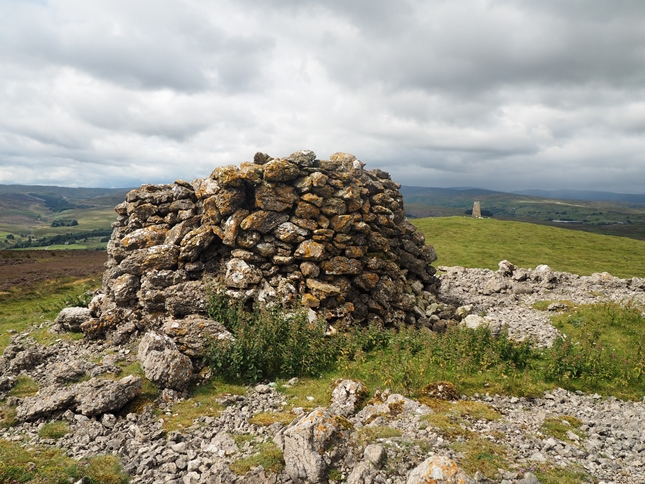 The large cairn on the summit with the trig point to the right
