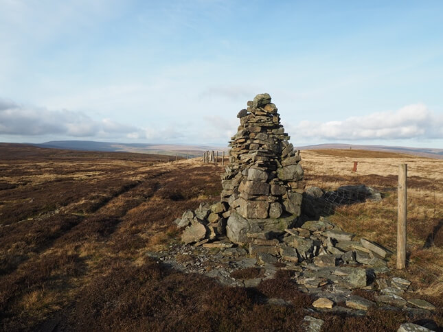 The summit cairn next to the fence