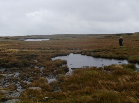 My friend Matt traversing the soggy plateau of East Baugh Fell passing one of the smaller East Tarns