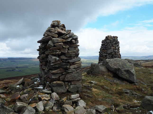 The two prominent cairns on the eastern end of the summit