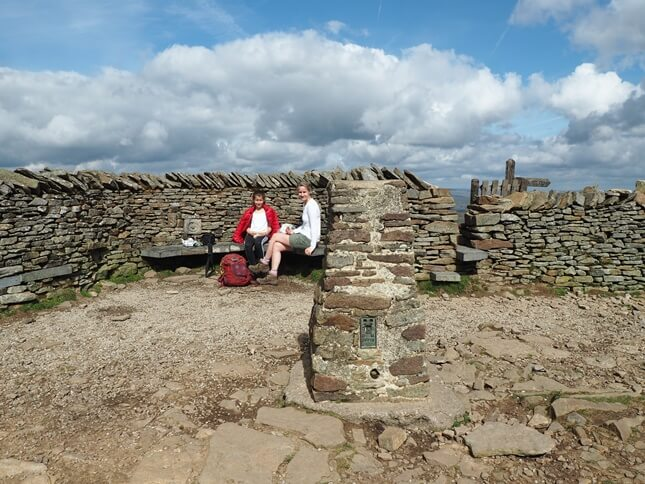 The trig point  on Pen-y-Ghent is located next to a wall and shelters