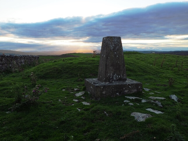 The Windy Hill trig point on a late summer evening with the tumuli just beyond