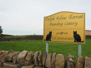 The Delph Farm trig point to the left of the cattery sign