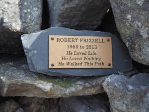 A small memorial stone inserted into the shelter