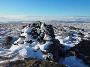 A snow covered cairn to the south of the summit