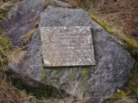 The memorial plaque on the stone on the opposite bank to the track