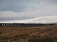 A train crosses the Ribblehead Viaduct with Whernside beyond