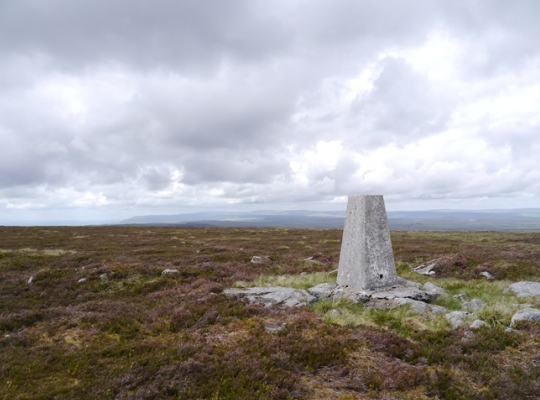 The trig point on Water Crag looking towards the North Pennines